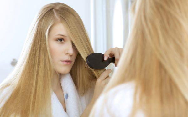 Девушка расчесывает густые волосы