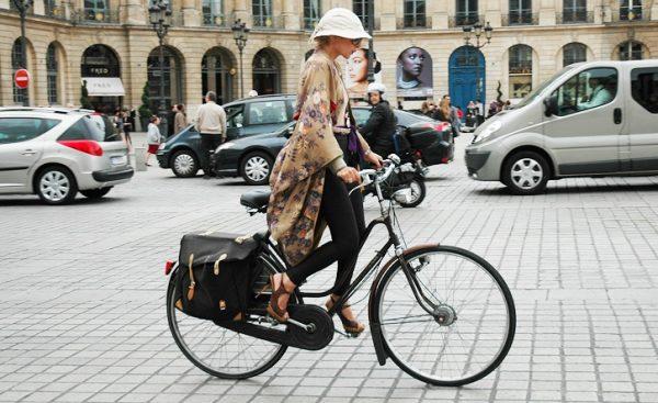 Девушка на велосипеде едет по городу